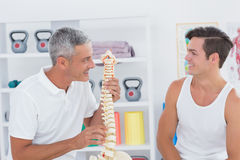 Doctor showing anatomical spine to his patient Royalty Free Stock Image