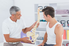 Doctor showing anatomical spine to his patient. In medical office stock photo