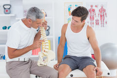 Doctor showing anatomical spine to his patient Royalty Free Stock Photography
