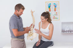 Doctor showing anatomical spine to his patient Stock Photos