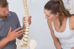 Doctor showing anatomical spine to his patient. In medical office royalty free stock photography
