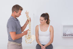 Doctor showing anatomical spine to his patient. In medical office stock photos