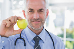 Doctor showing an apple. Smiling doctor showing a green apple Royalty Free Stock Photos