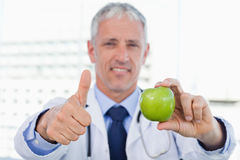 Doctor showing an apple with the thumb up. In his office Royalty Free Stock Image