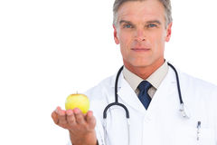 Doctor showing apple. To the camera Stock Photos