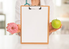 Doctor showing blank clipboard apple and donut. Closeup on medical doctor woman showing blank clipboard apple and donut Royalty Free Stock Photography