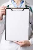 Doctor showing blank clipboard Royalty Free Stock Images