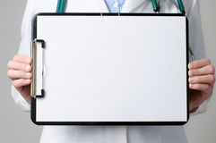 Doctor showing blank clipboard Stock Photo