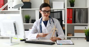 Doctor showing body parts on wooden model of man