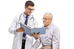 Doctor showing a book to an elderly patient. Isolated on white background Stock Photos