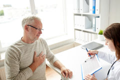 Doctor showing cardiogram to old man at hospital Stock Photo