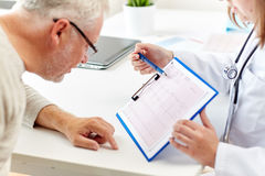 Doctor showing cardiogram to old man at hospital Stock Images