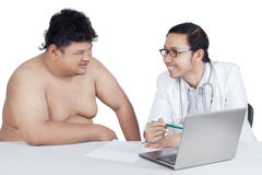 Doctor showing the check up result. Portrait of male doctor showing the check up result to an overweight man, isolated on white background Stock Photo