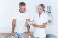 Doctor showing clipboard to her patient with crutch royalty free stock photos