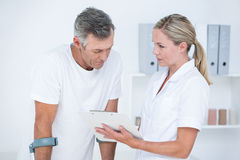 Doctor showing clipboard to her patient with crutch Royalty Free Stock Photo