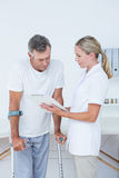 Doctor showing clipboard to her patient with crutch Stock Photography