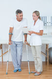 Doctor showing clipboard to her patient with crutch Stock Images