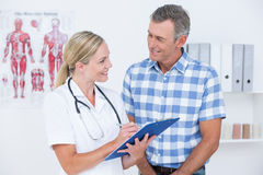 Doctor showing clipboard to her patient Royalty Free Stock Image