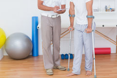Doctor showing clipboard to his patient with crutch Stock Images