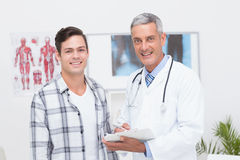 Doctor showing clipboard to his patient Stock Photo