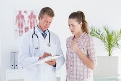 Doctor showing clipboard to his patient Royalty Free Stock Image