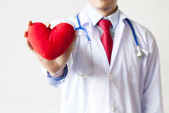 Doctor showing compassion and support holding red heart onto his chest in his coat. Doctor showing compassion and support holding red heart Royalty Free Stock Photography