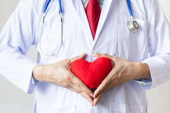 Doctor showing compassion and support holding red heart. Onto his chest in his coat Stock Images