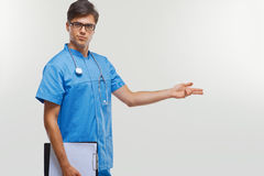 Doctor showing a copy space against white background. Royalty Free Stock Photos