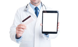 Doctor showing credit card and blank screen tablet Stock Photography