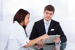 Doctor showing digital tablet to businessman Royalty Free Stock Photos
