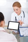 Doctor showing digital tablet to patient Stock Photos