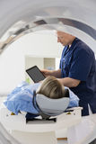 Doctor Showing Digital Tablet To Patient Undergoing CT Scan Stock Photography