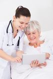 Doctor showing digital tablet to patient Royalty Free Stock Images