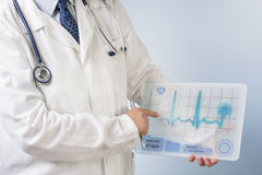 Doctor showing ecg. Physician showing ECG data on futuristic transparent tablet royalty free stock photos