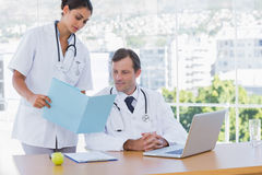 Doctor showing a folder to a colleague. Sat at his desk Royalty Free Stock Photos