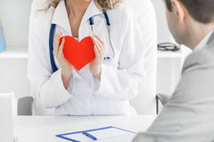 Doctor showing heart to patient Royalty Free Stock Photos