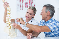 Doctor showing her patient a spine model Royalty Free Stock Photo