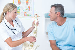 Doctor showing her patient a spine model. In medical office Stock Image