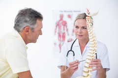 Doctor showing her patient a spine model Stock Photography