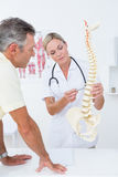 Doctor showing her patient a spine model Royalty Free Stock Photography