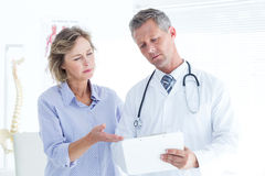 Doctor showing his notes to his patient Royalty Free Stock Photography