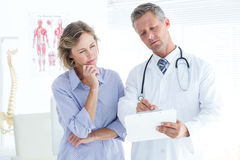 Doctor showing his notes to his patient Royalty Free Stock Photo