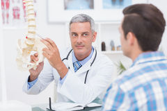 Doctor showing his patient a spine model Stock Images