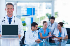 Doctor showing laptop with colleagues behind Stock Photo