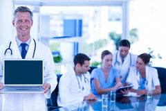 Doctor showing laptop with colleagues behind. In medical office stock image
