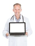Doctor showing laptop. Happy Mature Doctor Showing Laptop Over White Background royalty free stock photo