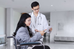Doctor showing medical report at disabled patient Stock Image