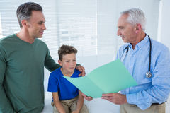 Doctor showing medical report to patient and his parent Royalty Free Stock Images