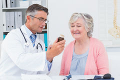Doctor showing medicine bottle to female patient. Male doctor showing medicine bottle to female patient in clinic Royalty Free Stock Image