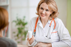 Doctor showing medicine can to patient in her Royalty Free Stock Image
